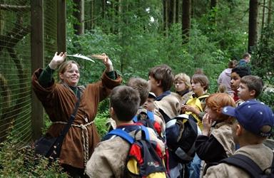 Eine Gruppe Kinder lauscht den Erklärungen der NEZ-Mitarbeiterin bei den Eulen