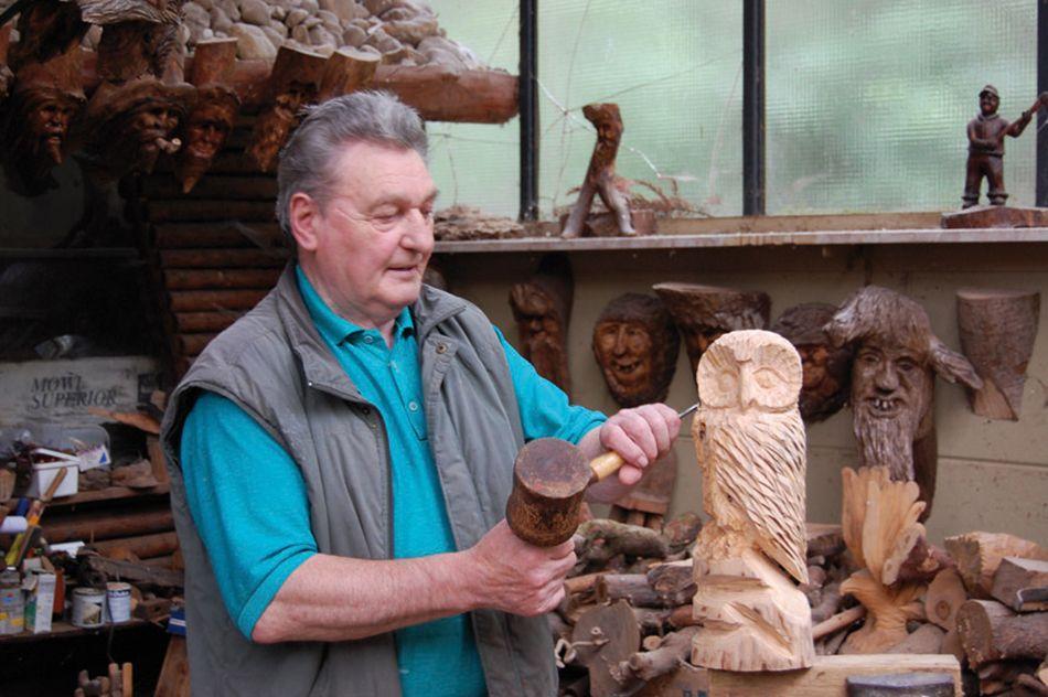 Kunsthandwerker arbeitet an Holzskulptur in der Kunsthandwerkerhalle im Wildpark Schwarze Berge