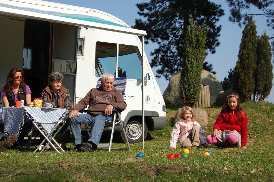 Familie spielt vor dem Wohnmobil beim Wildpark-Camping im Wildpark Schwarze Berge